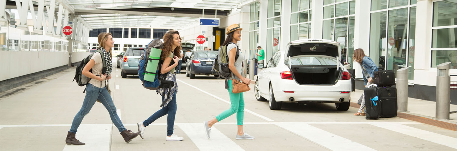 3 Females with luggage walking across the road